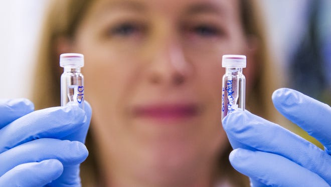 Forensic scientist Erika Canonico shows two vials of hydrocodone at the Arizona Department of Public Safety Crime Lab in Phoenix on Sept. 12, 2017.