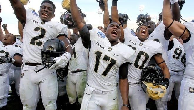 Army quarterback Ahmad Bradshaw, center, and his teammates celebrate their win against North Texas on Tuesday in the Heart of Dallas Bowl in Dallas, Texas.