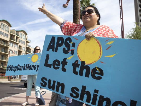 Jaqueline Perea, right, protests outside the Pinnacle West Capital Corp. annual shareholder meeting. Protesters want the company to disclose its political spending.