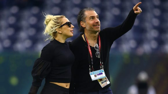 Lady Gaga and Christian Carino walk arm-in-arm on the field.