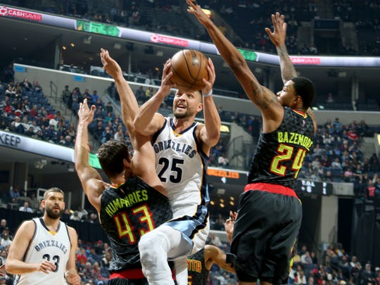 Memphis Grizzlies  Chandler Parsons, center, shoots defended by Atlanta Hawks Kris Humphries, left, and Kent Bazemore, right, at FedExForum on March 10, 2017.