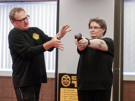 Tom Aydelott of Tampa, Florida, demonstrates the proper method of disengaging a firearm from a shooter's hands as Amy Ratekin volunteers as the shooter during an active shooter self-defense class at the Iowa Center for Higher Education building on Wednesday, April 11, 2018, in Des Moines.