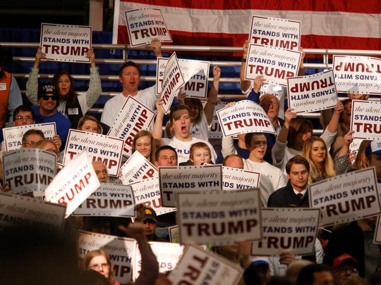Supporters of Republican presidential candidate Donald Trump holds up campaign signs prior to Trump's speech to supporters during a townhall-style meeting on Friday, Dec. 11, 2015, at the Varied Industries building at the Iowa State Fairgrounds in Des Moines.