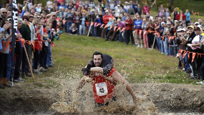 Elliot Storey races through the mud pit while carrying his wife, Giana Storey, both of Westbrook, Maine, to win the North American Wife Carrying Championship on at the Sunday River Ski Resort in Newry, Maine. They competed against 43 other couples to win the 17th annual championship. They covered the 278-yard obstacle course in 59.18 seconds.