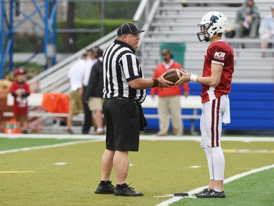 A referee hands the ball to Licking County's kicker