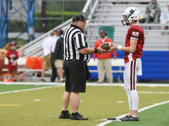 A referee hands the ball to Licking County's kicker to get the Muskingum Valley-Licking County All-Star Game underway in Duncan Falls last month.