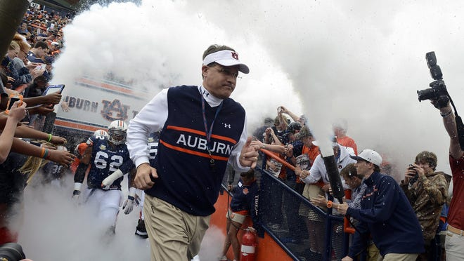 Coach Gus Malzahn and the Auburn Tigers running onto the field before the start of a game at Jordan-Hare Stadium.