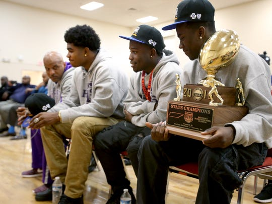 Trezevant head coach Teli White, Tywon Johnson, Joshua Reed and Tristian Jackson wait for a group photo to be taken following a press conference held at the Shelby County Schools Teaching and Learning Academy auditorium to recognize Trezevant, East and Whitehaven for their football state championships.
