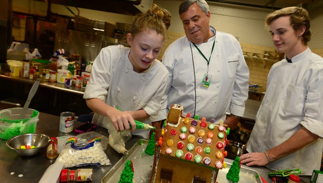 Chef Steve Musco, center, works with students Whitney Robertson, left, and Marcus Lilwea, right, as they work on gingerbread houses at the J. Harley Bonds Career and Education Resource Center in Greer on Tuesday.