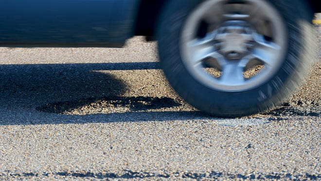 Motorists drive over potholes on Interstate 40. Potholes can cause hundreds of dollars of damage to vehicles.