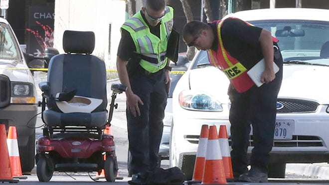 El Paso police look at the scene of a car-pedestrian accident at Mesa Street and Mills Avenue in Downtown El Paso on Wednesday afternoon. The pedestrian was riding in the motorized wheelchair at left.