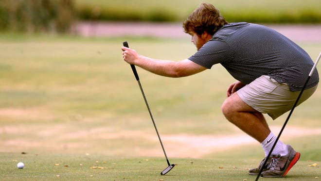 Oakland's Adam Dyke lines up a shot on the green at Indian Hills during the District 7-AAA golf tournament.