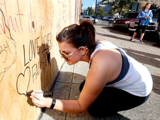 Johna Green writes a message of love with others  on