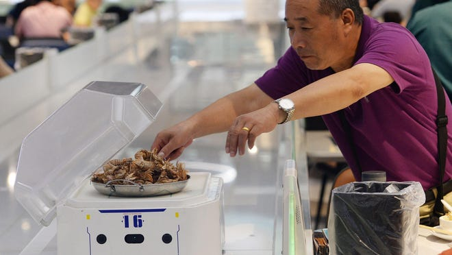 This photo taken on July 30, 2018 shows a man getting food from a robot at the ROBOT.HE restaurant in Shanghai, China.