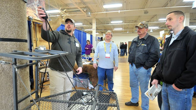 Exhibitors Curt Washa, left, and his father Bob, both of Highland, demonstrate a tree-stand gear to patrons Kevin Pliske and Curt Pliske during Sunday's Wisconsin Deer Classic and Hunting Expo at The Patriot Center in Rothschild.