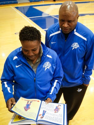 New Lansing Community College women's basketball coach Alayne Ingram, left, and her father, long-time LCC men's coach Mike Ingram, reminisce while looking through an old family book of basketball memories.