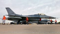 A 2015 file photo of a boneyard crew tows with an F-16