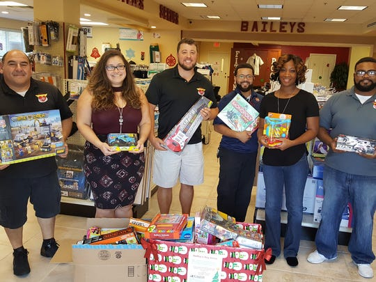 Baileys Medical Supply personnel gather around their toy donation to CASTLE.