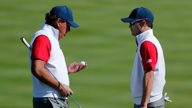 United States' Phil Mickelson, left, and teammate Zach Johnson chat on the second hole during their four ball match at the Presidents Cup golf tournament at the Jack Nicklaus Golf Club Korea, in Incheon, South Korea, Friday, Oct. 9, 2015.
