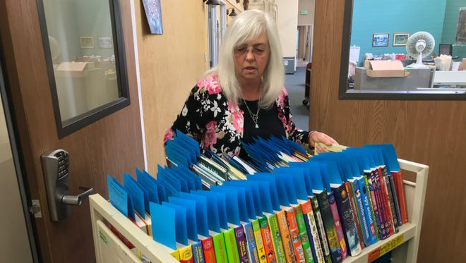 Children and Teen Services Manager Susan Mikula wheels a cart filled with donated children's books she's selected that will be added to the Ventura County library system's collection.