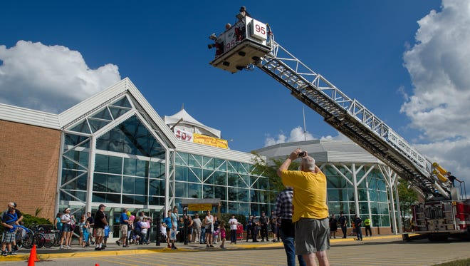 Radio personality Chuck Santoni gets lifted onto the roof of the Birchwood Mall Sunday, Sept. 18, 2016, during the annual Walk for Kids' Sake Roof Sit in Port Huron.