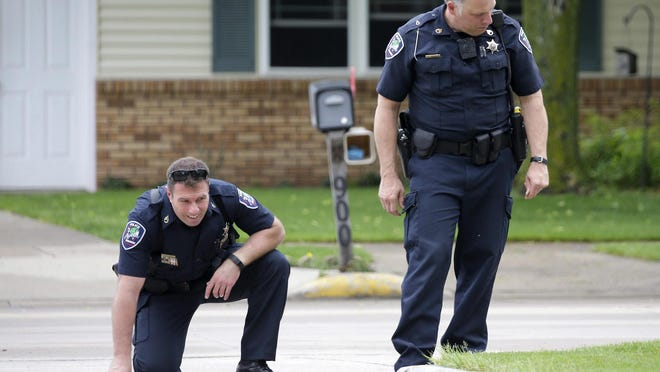 Officers survey the scene where an Appleton police officer and a bystander were shot and a suspect killed early Saturday near in the 900 block of S. Kensington Drive near Kensington Court.