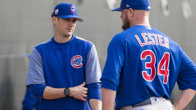 Chicago Cubs pitching coach Tommy Hottovy, left, and pitcher Jon Lester talk Feb. 15, 2019, during spring training in Mesa, Ariz.