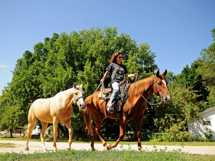 Shannon Olson, of White River, S.D., rides a horse while leading another through town on Monday, July 28, 2014, in White River, S.D.
