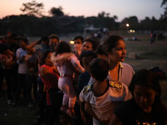 Central American migrant women and children stand in