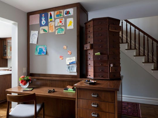 A home work space designed by Tamara Eaton features an oversized pin-board extending all the way to the ceiling, perfect for displaying all the newest kids artwork coming in. An antique rotating cabinet, right, also provides useful storage with unique flair.