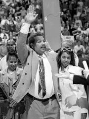 University of Memphis coach Larry Finch waves his appreciation to the fans after being presented with his jersey number March 1, 1997 at the Memphis vs. Cincinnati game. With Finch is his daughter Shanae. It was the final regular-season game for the coach.