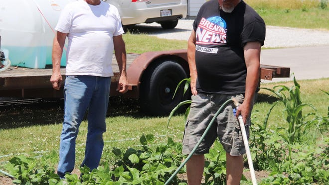 Shawn Trainor waters some plants at a garden on Forrest Street as Steve Mattingly supervises Thursday. Mattingly said the food produced from the garden will go to a food pantry.