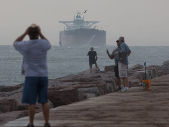 Spectators watch as the largest tanker to dock in a