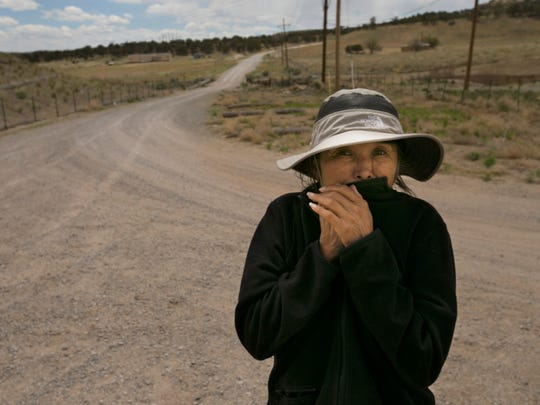 Lillie Lane, the public-information officer for the Navajo Nation Environmental Protection Agency, uses her fleece to cover her face as high winds pick up dust by abandoned uranium mines at Church Rock, N.M., on the Navajo Reservation.