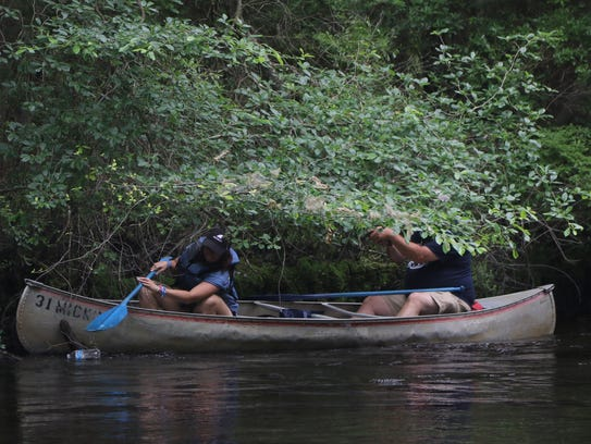 This canoe crew ducks under some of the trees that