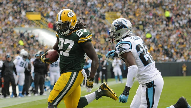 Green Bay Packers running back Eddie Lacy (27) runs in for a touchdown past Carolina Panthers cornerback Antoine Cason (20) in the first quarter during Sunday's game at Lambeau Field. Evan Siegle/Press-Gazette Media