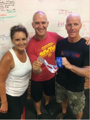 John Fuller, at right, shows off his silver medal to his Crossfit Katana gym owner J.P. Pocock, his trainer at CrossFit Katina gym on North Mulberry Street. At left is Abbie, John's wife.