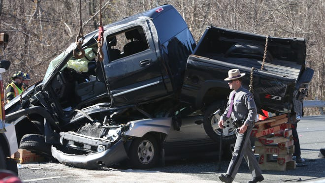 A New York state trooper surveys the damage done at an accident in which a pickup truck traveling northbound on Interstate 684 jumped the center guardrail striking several vehicles and landing on one of them in Katonah April 24, 2014. A total of three people were injured and transported to local hospitals.
