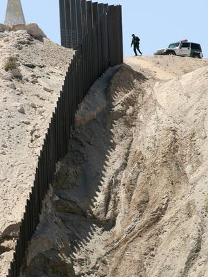 A Border Patrol agent walks by the controversial new border fence being built in Sunland Park, New Mexico.  Photo by Mark Lambie