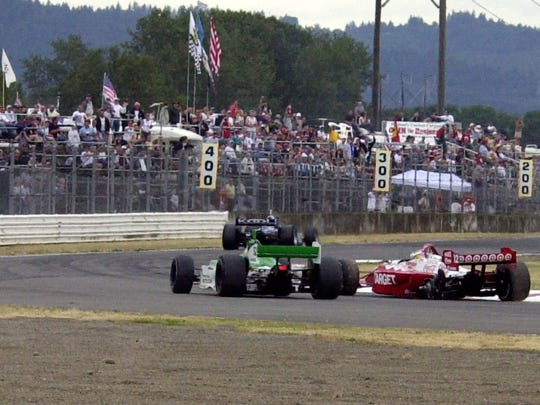 Kenny Brack (far right) loses his left rear wheel and the lead of the CART race at Portland International Raceway in 2002.