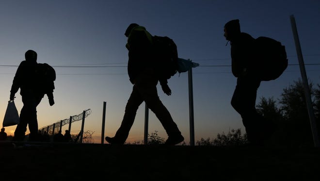 People cross the borderline on their way to a temporary holding center for migrants in the early morning at the border between Serbia and Hungary on Sept. 14.