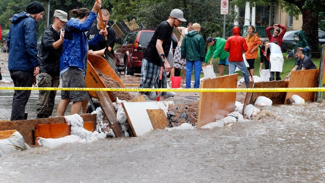 Residents try to divert floodwater from their apartments in Boulder, Colo., on Sept. 12.