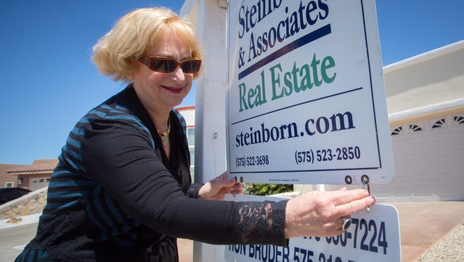 Evelyn Bruder, who's been a realtor for over 30 years, adjusts her sign outside a home for sale in The Missions neighborhood of Las Cruces, March 25, 2016.