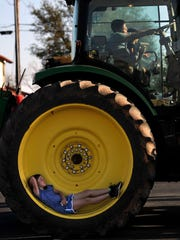 Jaci Welsh, 7, reclines in the wheel as Jared Hernandez, 8, pretends to drive the tractor with his friend Bobby Rangel, 6. Snyder's Calvary Baptist Church held a Touch-A-Truck event Wednesday April 4, 2018, the evening featured ten service vehicles for children in the church youth group to inspect up-close and crawl around on.