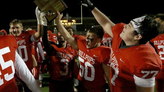 McPherson players Sam Becker (80), Jayton Alexander (3), Eli Clarke (50) and Drew Hanken (77) celebrate their 28-21 victory over Buhler during the 4A sectional playoff game Friday night.