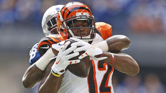 Cincinnati Bengals wide receiver Mohamed Sanu is wrapped up by Indianapolis Colts cornerback Greg Toler  after catching a pass Sunday, Oct. 19.