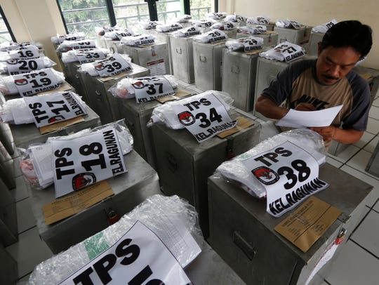 An election worker checks ballot boxes before they