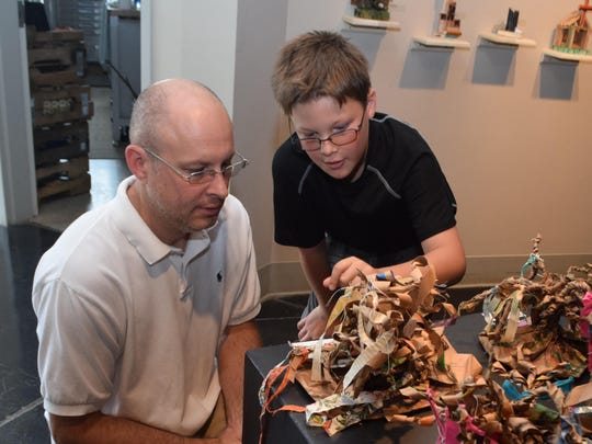 J.D. Descant (right) shows his father Derek Descant the character creation he made in River Oaks Art Center's summer camp program.