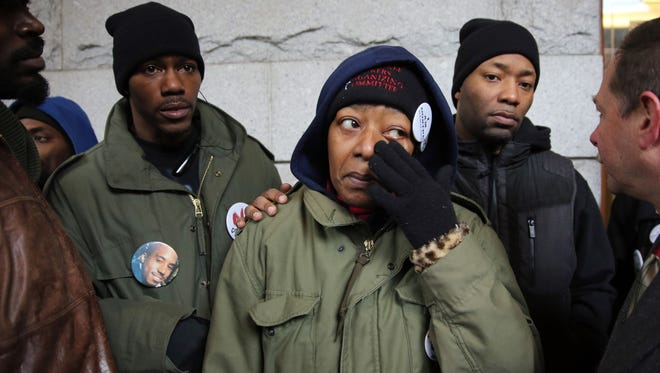 Maria Hamilton, mother of Dontre Hamilton, wipes a tear away after her son, Nate Hamilton (left), family and supporters of Dontre Hamilton spoke outside the Federal Courthouse on E. Wisconsin Ave. about the decision not to charge Milwaukee police officer Christopher Manney in the fatal shooting of Dontre Hamilton in April at Red Arrow Park in 2014.