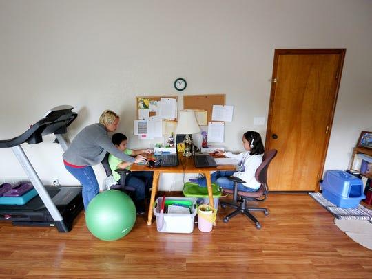 Heidi Bumanlag looks over the school work of her children